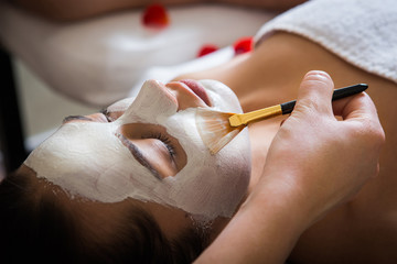 young beautiful woman with facial mask, spa treatment