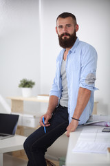 Portrait of male designer in hat with blueprints at desk