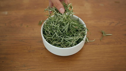 Bowl with rosemary on a wooden table