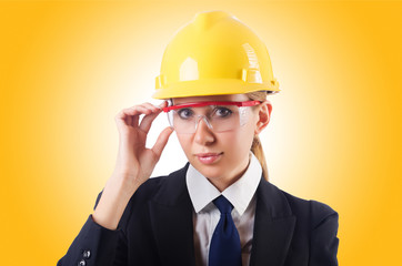 Young businesswoman with hard hat on white