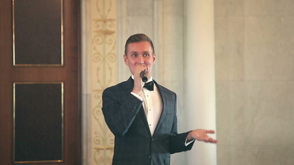 entertainer leads event speaks into the microphone