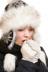 Winter vacation. Freezing girl warming her hands.