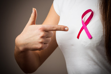 woman in t-shirt with pink cancer ribbon pointing