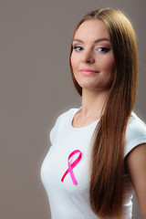 woman in t-shirt with pink cancer ribbon on gray