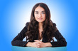 Young businesswoman sitting at desk on white