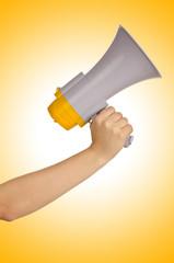 Hand holding loudspeaker on white