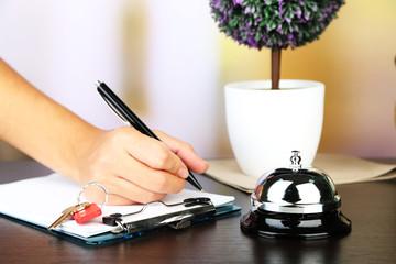 Female hand  writing in Hotel guest book