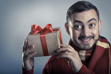 Cheerful man shaking the gift box and smiling.