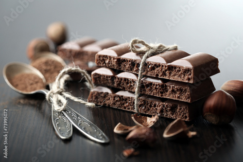 canvas print picture Tasty porous chocolate with nuts on table, close up