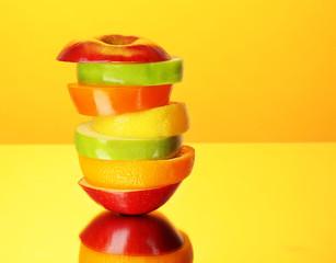 Fresh sliced fruit on colorful background