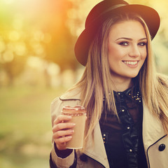 Young woman with fedora hat and coffee cup in park in autumn