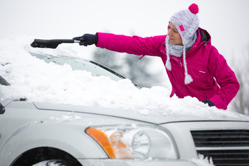 Woman removing snow from car