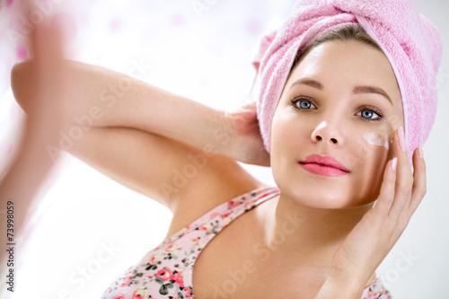 Leinwanddruck Bild Young girl putting cream on her face