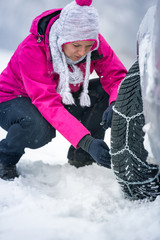 woman putting winter chains on car