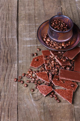 Coffee beans and chocolate over wooden background