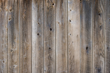 Vetical worn fence boards with gray finish with knots