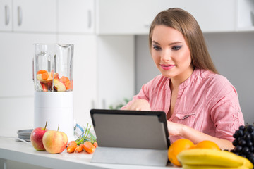 woman in kitchen reading a recipe from a digital tablet