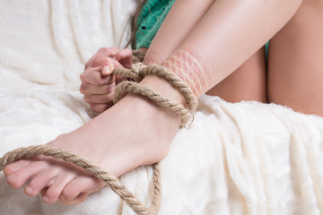 Slender woman's legs tied with rough rope