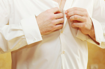 Elegant young man buttoning a shirt