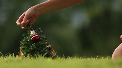girl decorates the Christmas tree with accessories
