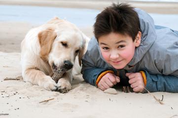 Boy and retriver on the beach