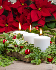 Lit candles with evergreens and poinsettias