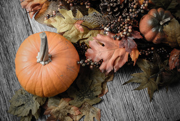 Pumpkin and Fall Leaves on Rustic Wood Background
