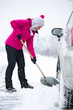 Woman  shoveling snow around the car