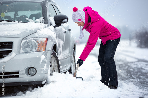 Leinwanddruck Bild woman shoveling snow from her car