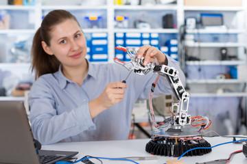 schoolgirl adjusts the robot arm model