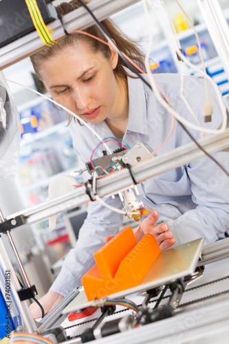 Leinwanddruck Bild girl student makes the item on the 3D printer