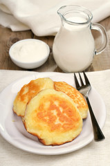 Fritters, milk jug and sour cream on rustic table