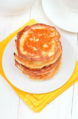 Fritters with honey on white plate