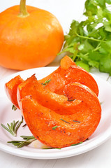 Baked pumpkin slices on white plate