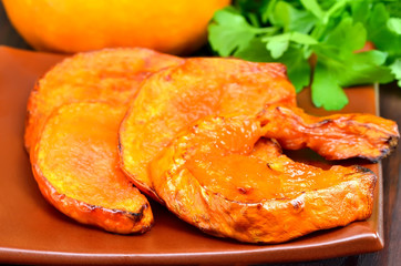 Slices of baked pumpkin on plate, close up view