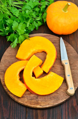 Pumpkin slices and knife on cutting board
