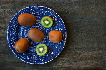 Kiwi on the blue plate on the dark wooden table