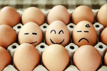 Chicken eggs with drawn face emotions.