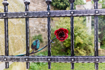 Iron gate with red rose and crucifix