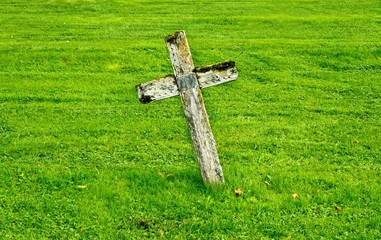 Old wooden christian cross at the graveyard.
