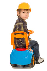 little boy on a toy car and a helmet
