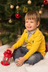 little boy sits near a Christmas tree