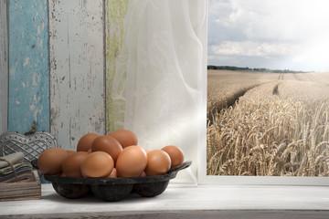 Frische Eier auf dem Fensterbrett mit Getreidefeld