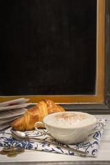 Milchkaffee und Croissant , Schreibtafel im Hintergrund