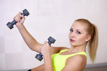 Active beautiful sports girl lifting dumbbells