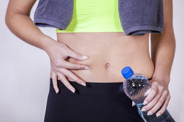Woman after fitness training, pinches fat on the belly