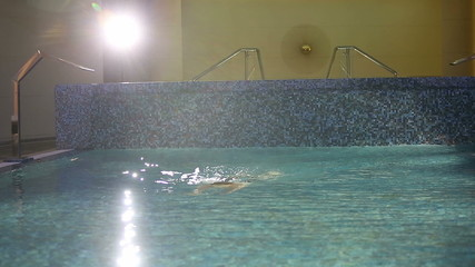 The rich man is swimming in the pool. Close up