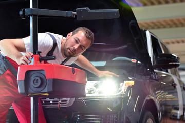 Lichttest // Automotive mechanic makes light test in workshop