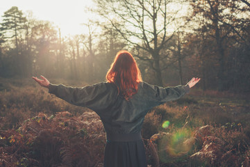 Young woman raising her arms in forest at sunset