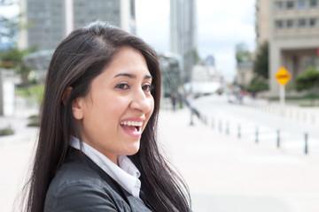 Fröhliche Frau mit langen schwarzen Haaren in der Stadt